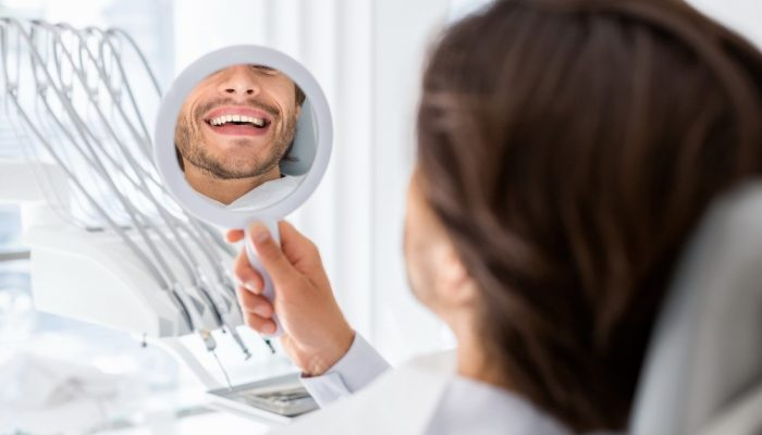 satisfied-patient-checking-smile-at-mirror-in-dent